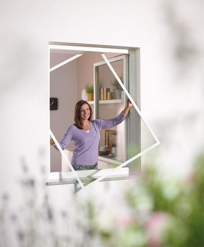 Frau mit festem Insektenschutzrahmen am Fenster